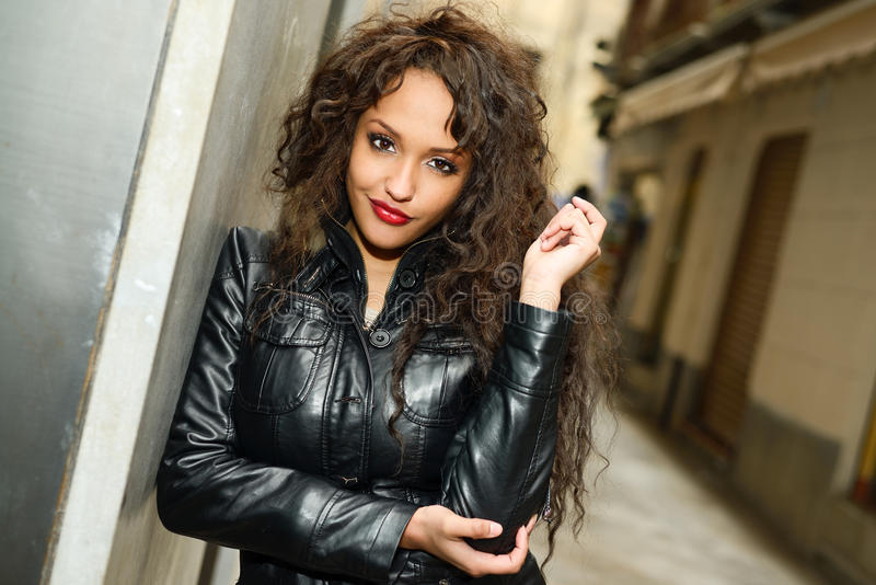 Attractive black woman in urban background wearing leather jacket. Portrait of attractive black woman in urban background wearing leather jacket royalty free stock photo