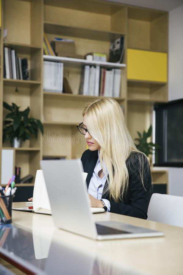 Attractive blond businesswoman working in modern office stock images