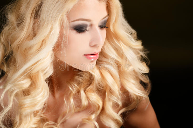 Portrait of an attractive blond woman with long curly hair, isolated on black studio shot royalty free stock images