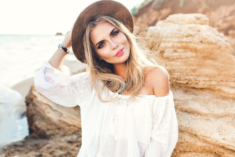 Portrait of attractive blonde girl with long hair posing on deserted beach. She wears white shirt, hat, ornamentation. She is smiling to the camera royalty free stock photography
