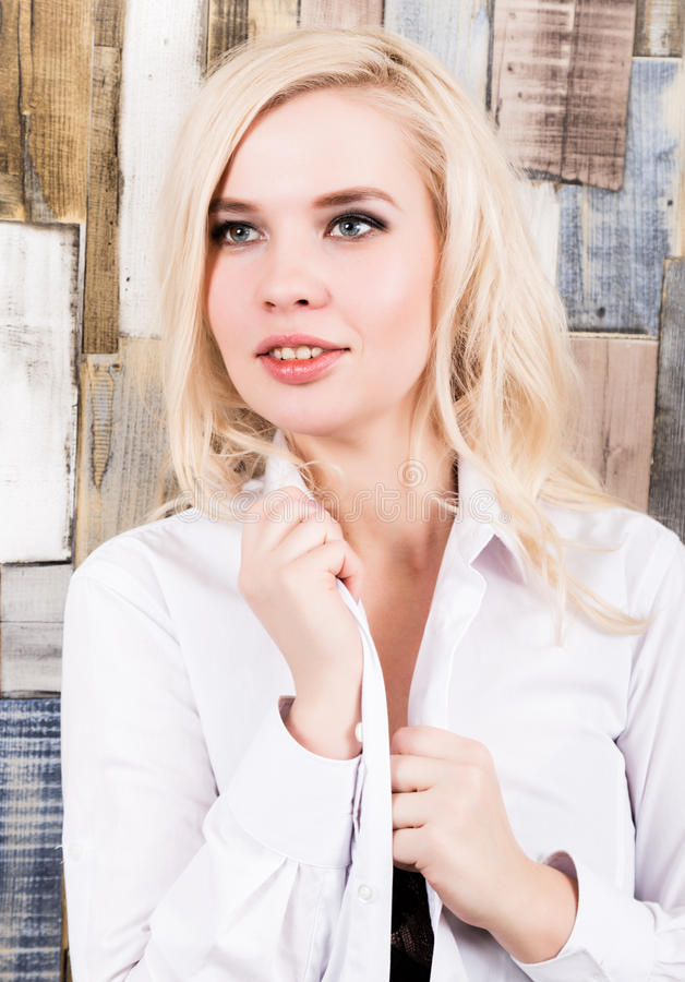 Portrait of attractive blonde girl standing on wood wall background. She has blue eyes and dressed in a man`s shirt stock image