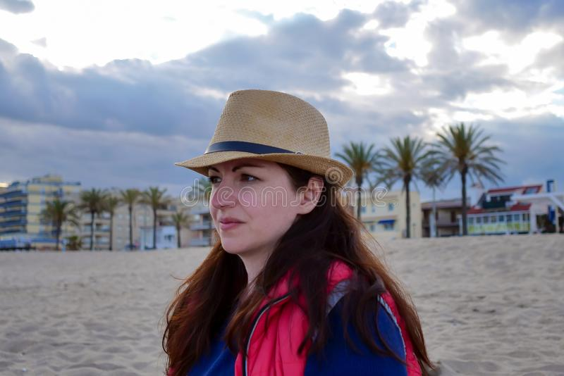 Portrait of attractive brunette in evening hat on the beach royalty free stock photos