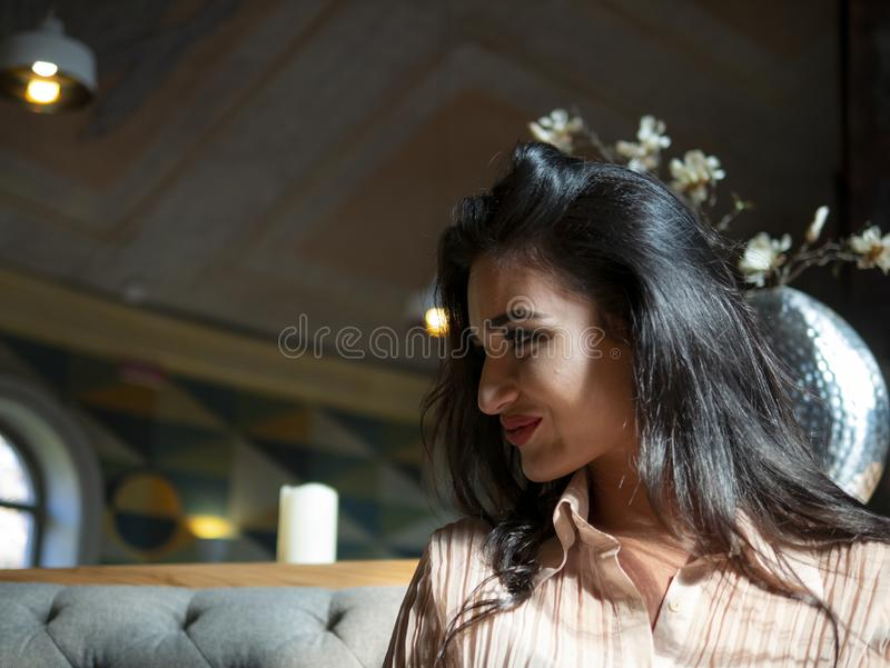 Portrait of attractive brunette girl with a beautiful smile indoors stock photography