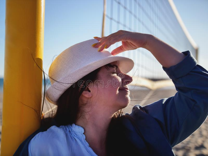Portrait of an attractive brunette girl in a white hat stands near a volleyball net on the beach royalty free stock image