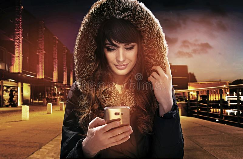 Portrait of an attractive brunette holding a smartphone stock photo
