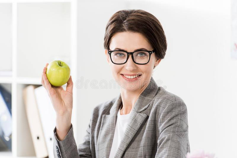 Portrait of attractive businesswoman holding apple in office and looking. At camera stock photos
