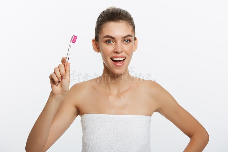 Portrait of attractive caucasian smiling woman brunette isolated on white studio shot head and shoulders face skin hand. Hair looking at camera with tooth brush stock photo