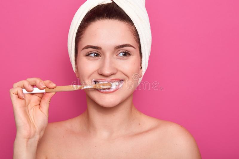 Portrait of attractive caucasian smiling woman brushing her teeth  over pink studio wall, standing with white towel on stock photography