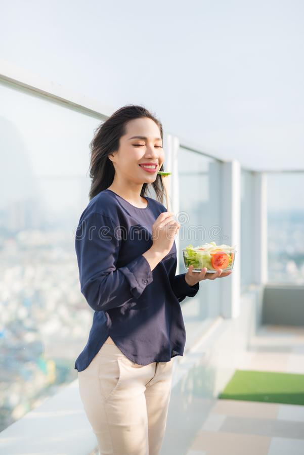 Portrait of attractive caucasian smiling woman eating salad on a sunny summer day sitting on green grass in park, focus on fork royalty free stock images