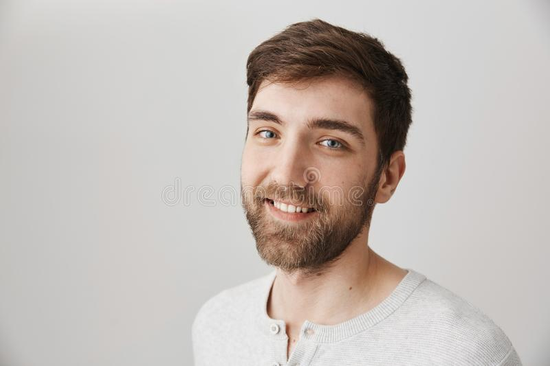 Portrait of attractive charming bearded guy with kind smile standing half-turned over gray background, expressing. Confidence and friendliness. Boyfriend picks stock images
