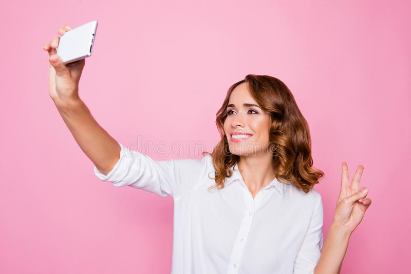 Portrait of attractive charming smiling woman taking a selfie on. Her smartphone and showing v-sign, isolated on bright pink background royalty free stock image
