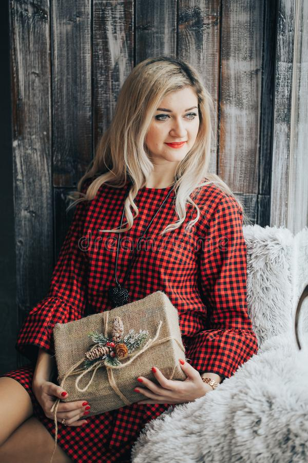 Portrait of attractive cheerful girl with playful look. Blonde hair beautiful woman with present in her hands. Young stock photography