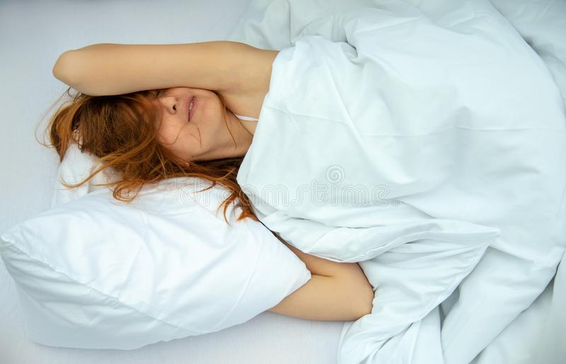 Portrait of an attractive, content, young, red-haired woman lying relaxed in bed, enjoying and snuggling stock photo