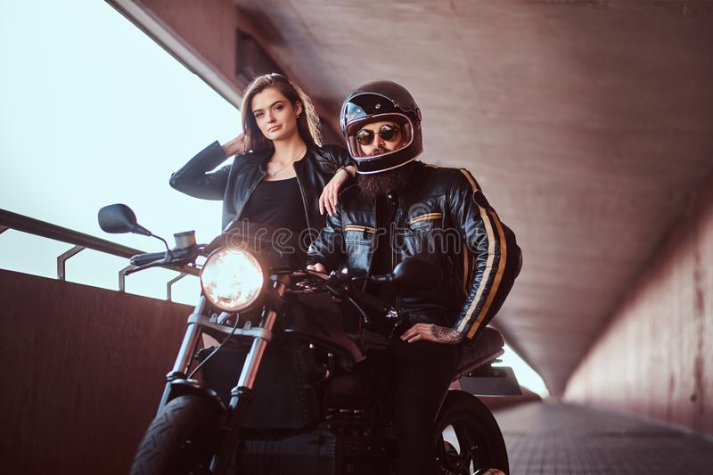 Portrait of an attractive couple - brutal bearded biker in helmet and sunglasses dressed in a black leather jacket stock images
