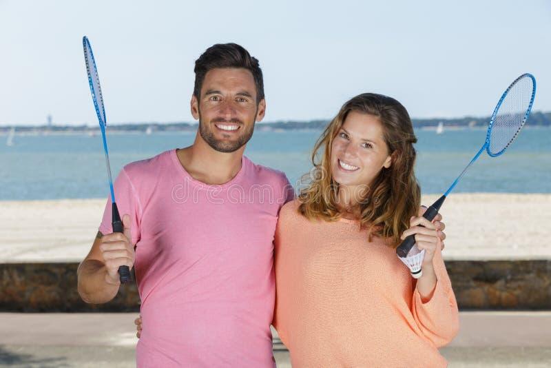 Portrait attractive couple holding badminton rackets stock image