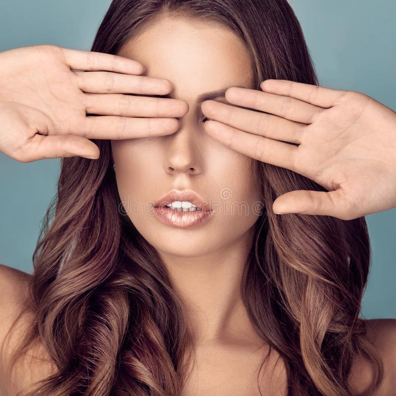 Woman closing eyes. Portrait of attractive curly woman closing eyes with two hands stock photo