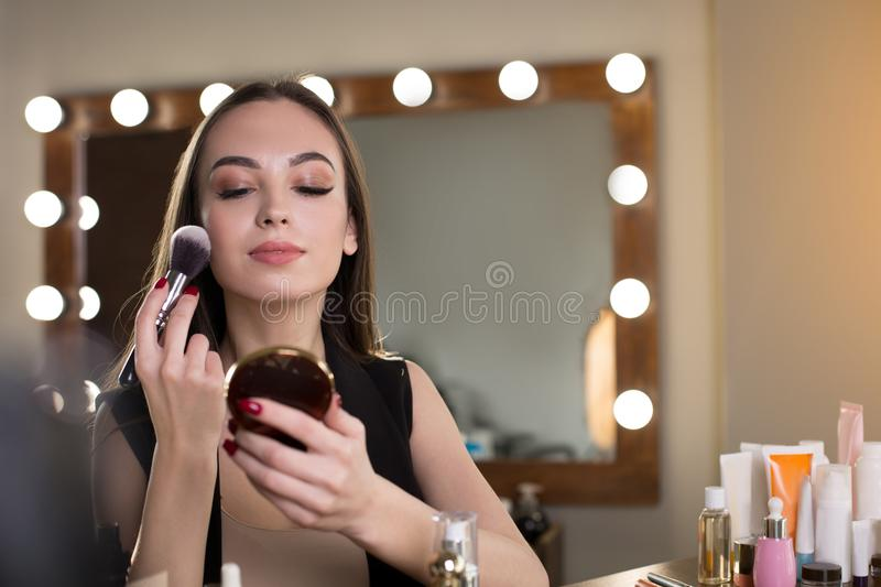 Pleasant young woman is powdering her face stock photos