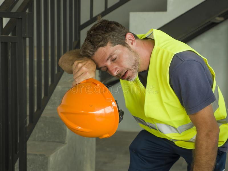 Portrait of attractive and exhausted construction worker in helmet and vest at building site taking a breath during a hard working stock images
