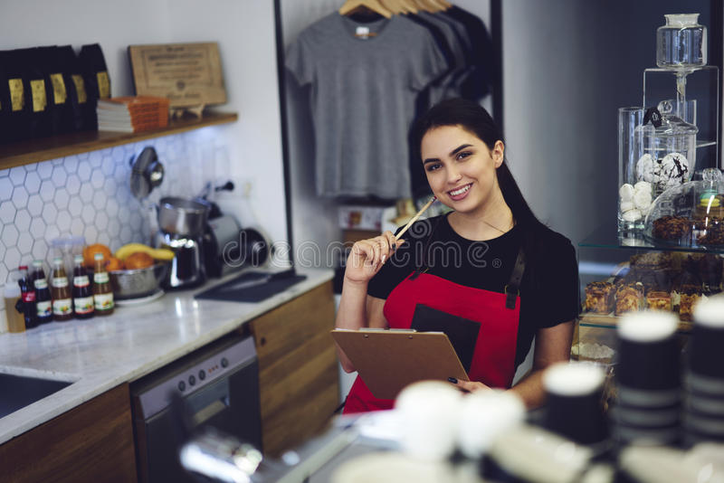 Portrait of attractive female barista working in cafeteria. Portrait of charming female barista in apron checking documentation before opening prepare everything stock photo