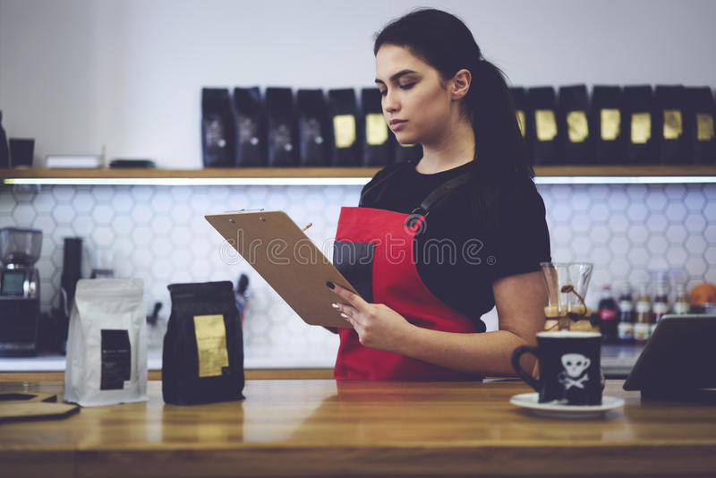 Portrait of attractive female barista working in cafeteria. Confident attractive female administrative manager making revision checking amount of products royalty free stock photography