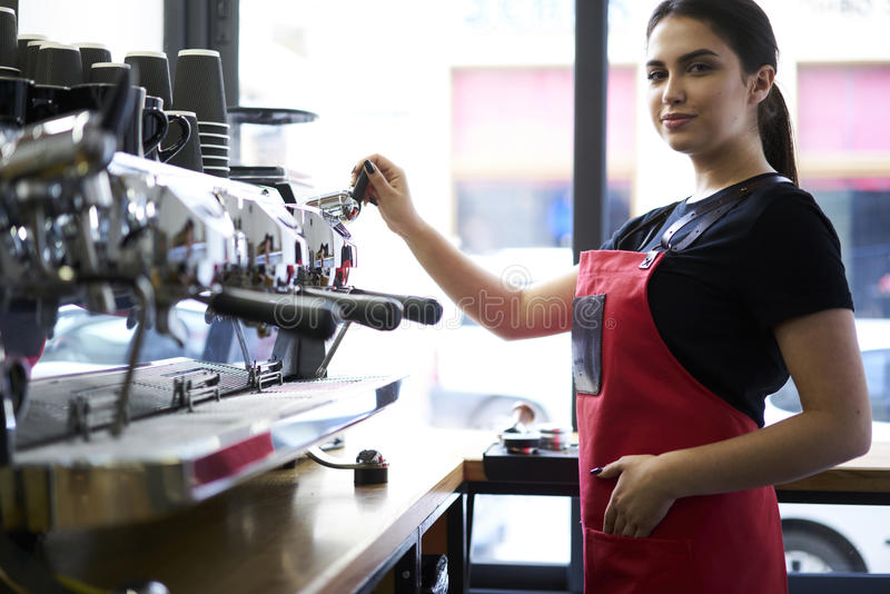 Portrait of attractive female barista working in cafeteria stock image