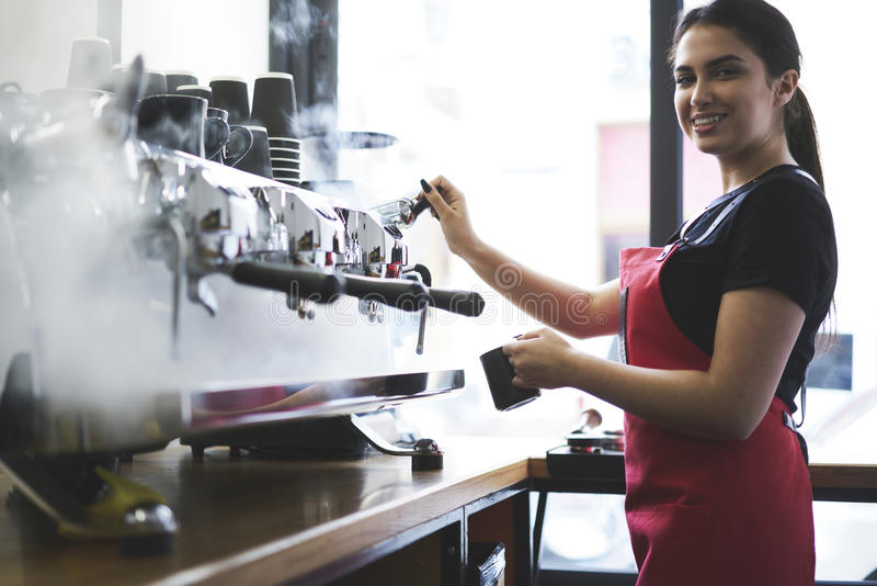 Portrait of attractive female barista working in cafeteria. Smiling busty female barista using professional coffee machine enjoying job in cafe improving skills stock photography