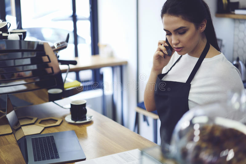 Portrait of attractive female barista working in cafeteria stock photography