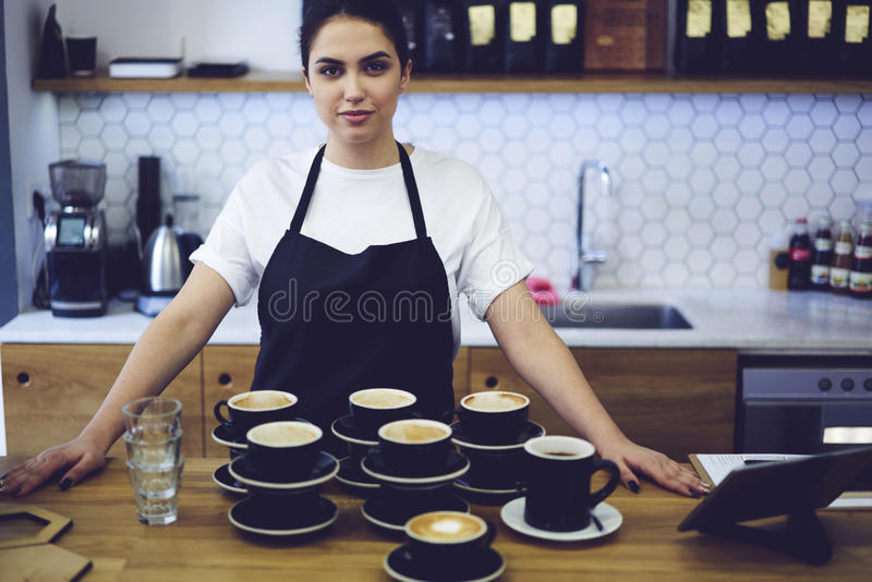 Portrait of attractive female barista working in cafeteria royalty free stock image