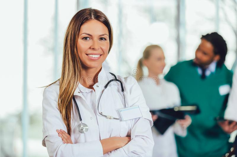 Attractive female doctor on hospital corridor looking at camera smiling. Portrait of attractive female doctor on hospital corridor looking at camera smiling stock photography