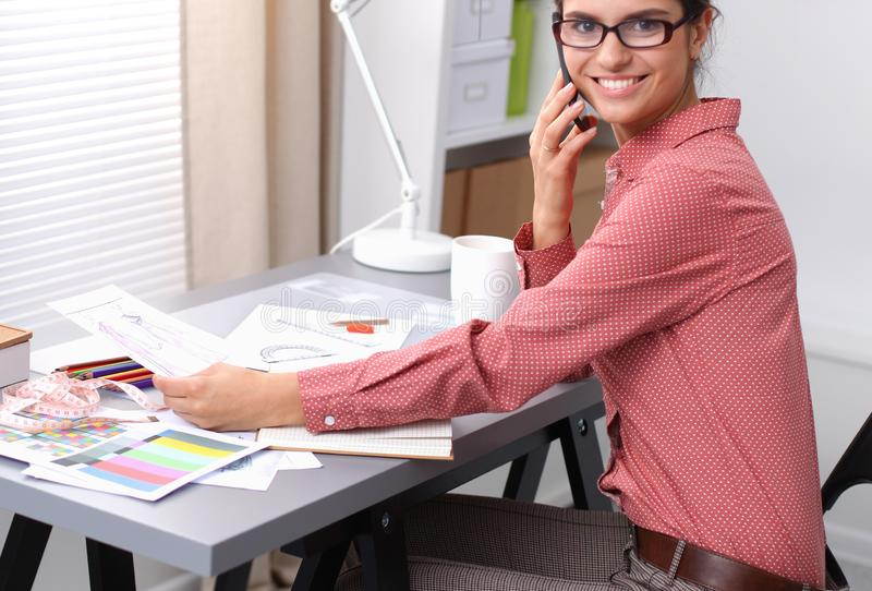 Portrait of attractive female fashion designer sitting at office desk, smiling royalty free stock photography