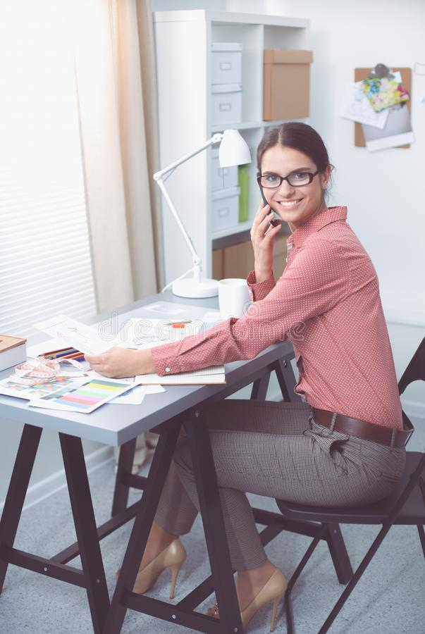 Portrait of attractive female fashion designer sitting at office desk, smiling stock photos