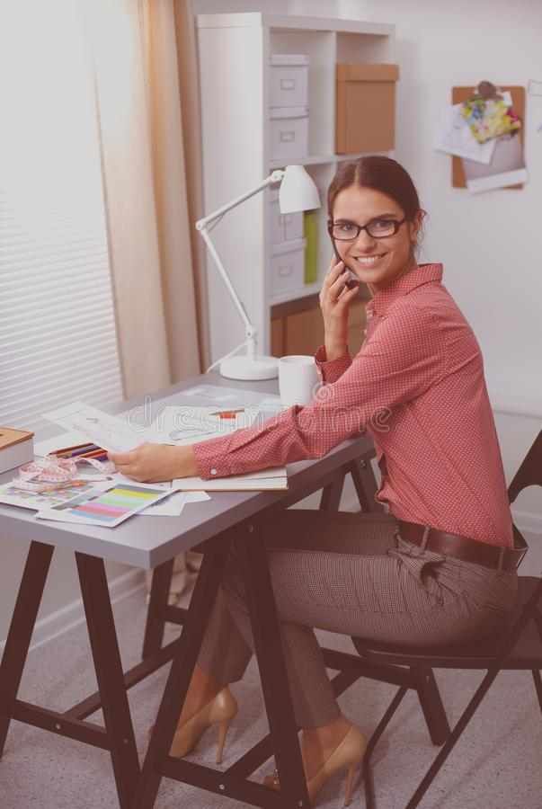 Portrait of attractive female fashion designer sitting at office desk, smiling stock images