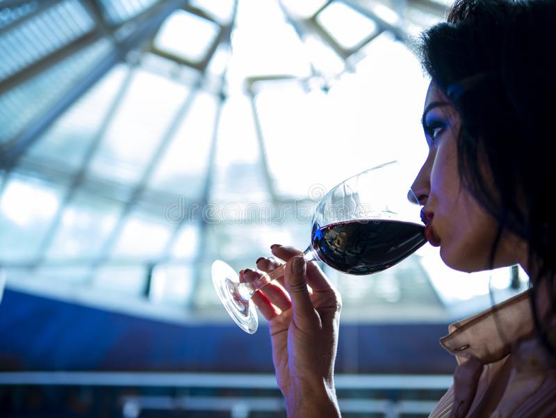 Portrait of an attractive girl with beautiful lips who drinks red wine from a glass stock photos