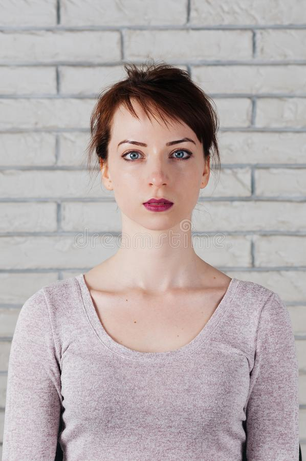 Portrait of attractive girl with eyes closed, peaceful look. A pretty girl with eyes closed as in meditation, peaceful look, with white brick wall in the royalty free stock photo