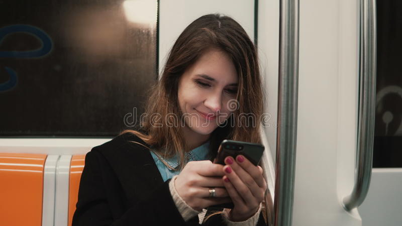 Portrait of attractive girl in subway train using smartphone. Young woman chatting with friends and smiling. stock images