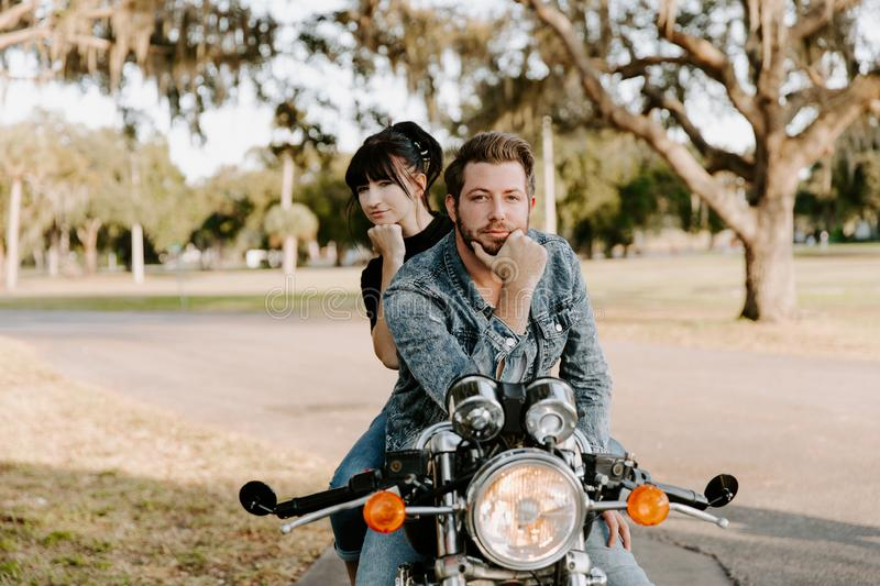 Portrait of Attractive Good Looking Young Modern Trendy Fashionable Guy Girl Couple Riding on Green Motorcycle Cruiser Old School stock photos
