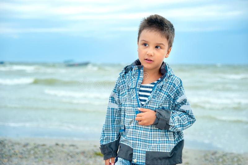 Portrait of a attractive handsome smiling boy in a vest. Funny cute child in summer by stormy sea weather. Happy childhood. Activity, adorable, baby, beach stock images