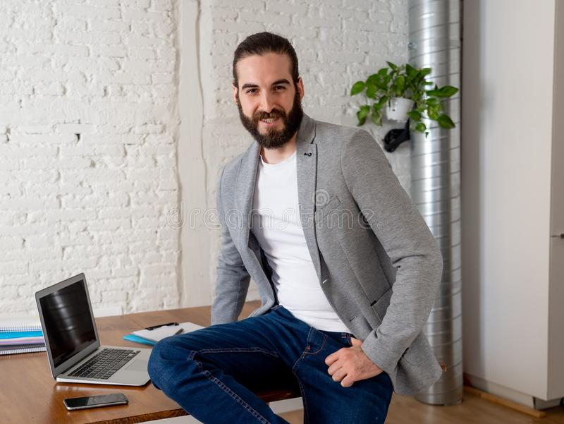 Portrait of attractive happy hipster businessman in modern fashion home office stock photo