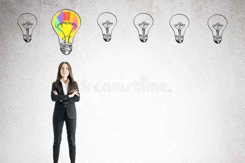 Idea and purpose concept. Portrait of attractive happy young european businesswoman with folded arms and drawn lamps standing on concrete wall background. Idea stock image