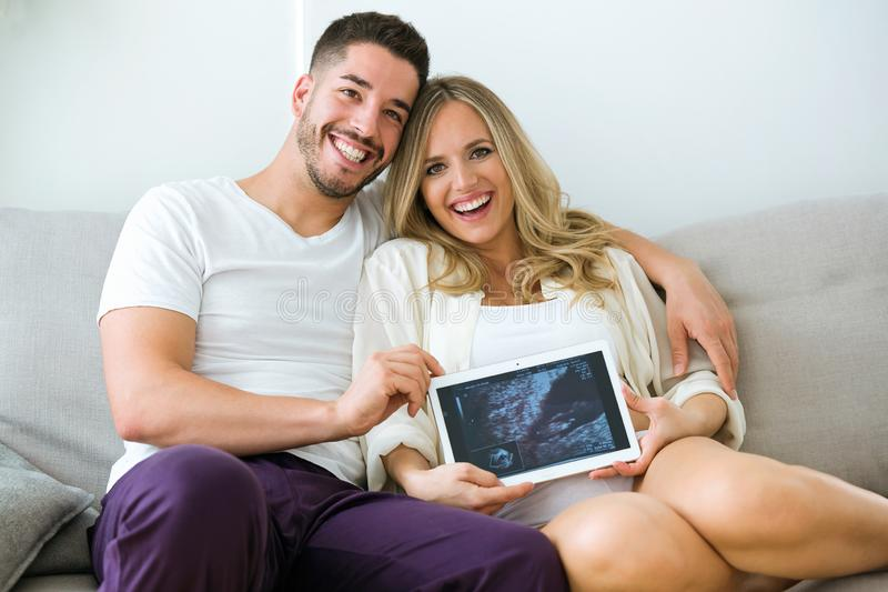 Attractive happy young man and pregnant smiling woman looking at camera while holding digital tablet at home. stock photos