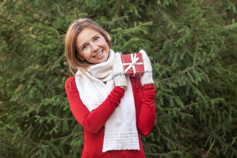 Portrait of attractive happy young woman with Christmas gift box in her hands stock photo