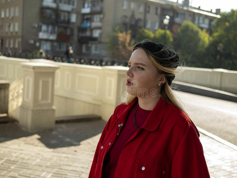 Portrait of an attractive hipster blonde girl in a knitted black hat and red jacket outdoors.  royalty free stock photo