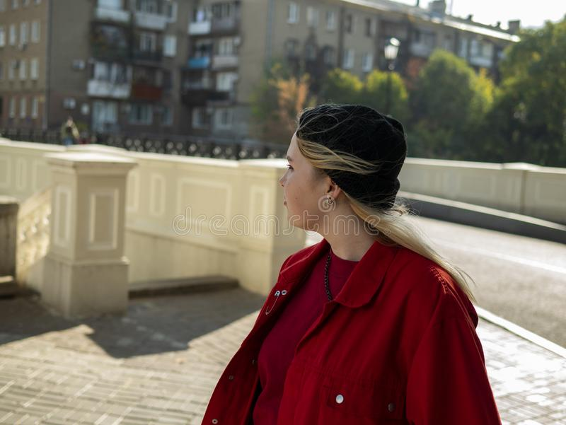 Portrait of an attractive hipster blonde girl in a knitted black hat and red jacket outdoors.  royalty free stock photography