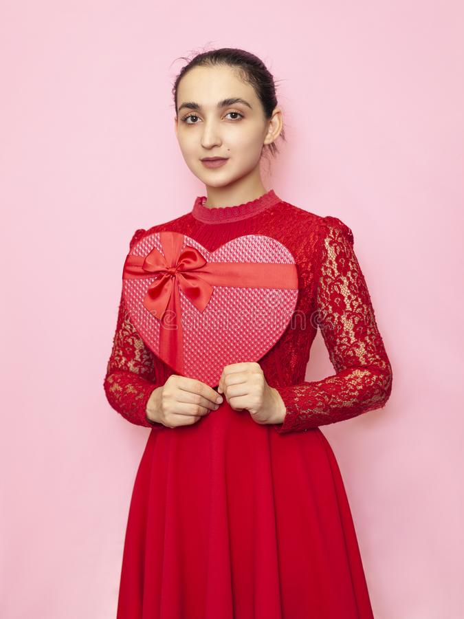 Portrait of attractive Hispanic woman holding giftbox. Valentines day gifts. Beautiful middle-eastern girl receives heart-shaped royalty free stock photography