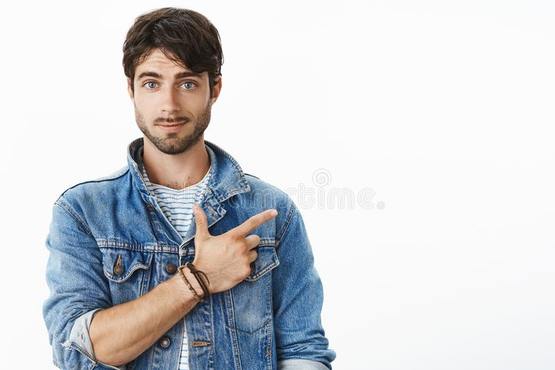 Portrait of attractive hispanic young male with beard and blue eyes pointing at upper right corner smiling asking stock photography