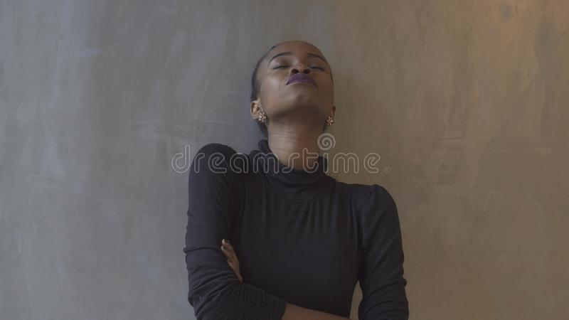 Portrait of the attractive isolated african girl leaning on the gray wall with closed eyes and arms crossed. royalty free stock photo