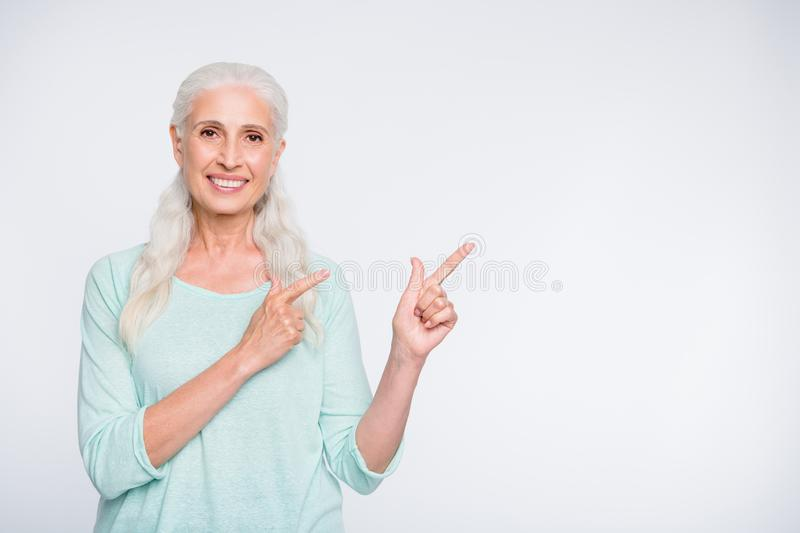 Portrait of attractive lady pointing promotion with her index finger wearing teal jumper isolated over white background stock photos