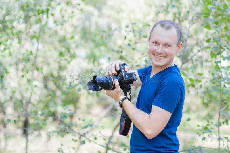 Portrait of attractive male photographer wearing blue t-shirt outdoors on Summer day. Young man with a DSLR camera in hands royalty free stock image