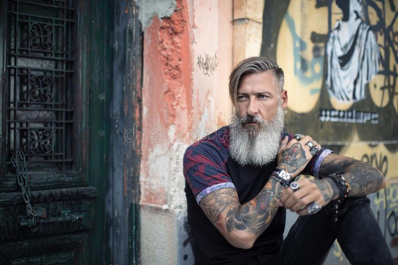 Portrait of an attractive man with a beard and tattoos in front of a green door royalty free stock photos