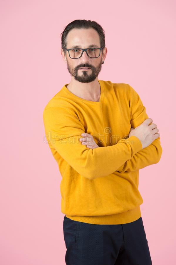 Portrait of attractive man with crossing hands on chest in ochre cardigan and glasses on pink background royalty free stock images